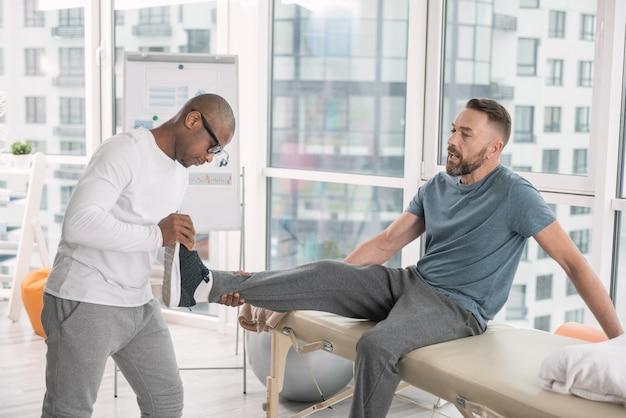 Развитие мышц. симпатичный брутальный мужчина сидит, поднимает ногу и развивает мышцы