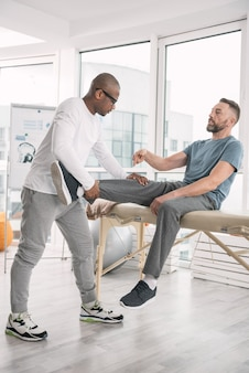 Muscle development. nice professional therapist standing in front of the patient while holding his leg
