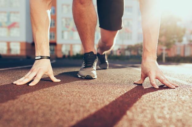 Мышцы, руки, солнечный свет, ноги в кроссовках сильного парня на стадионе утром. у него подготовка к старту.