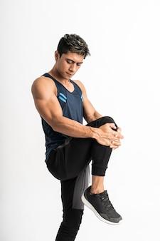 측면을 향한 운동복을 입은 근육 남자는 배 앞에서 다리를 들어 다리 스트레칭을합니다.