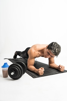 Muscle man without clothes do plank exercises with a mat next to the bottle and dumbbell