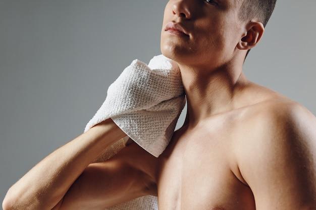 筋肉の裸の男がトレーニング汗を拭く円を描くビュー
