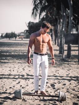 Мускулистый мужчина без рубашки на пляже. тренировка со штангой
