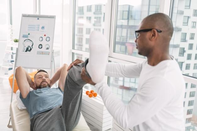 Мышечная терапия. приятный красавец, лежа на медицинской кушетке, развивая мышцы