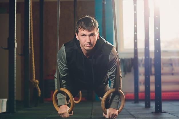 体操リングのジムで激しいトレーニングを行う筋肉運動エクササイズ男。
