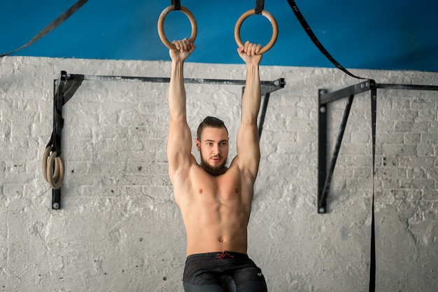 Muscle-up exercise athletic man doing intense workout at gym on gymnastic rings