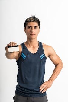 彼の手に現在のクレジットカードで前方を向いたスポーツウェアスタンドを着て筋肉の若い男