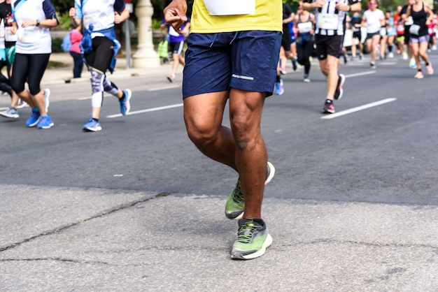 Muscled legs of a black male runner competing in an amateur race through the streets of valencia, spain.