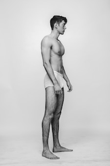 Muscled model standing full-height in trunks on the white