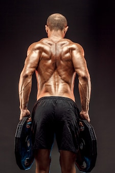 Muscled shirtless male model showing his back muscles on dark wall isolate.