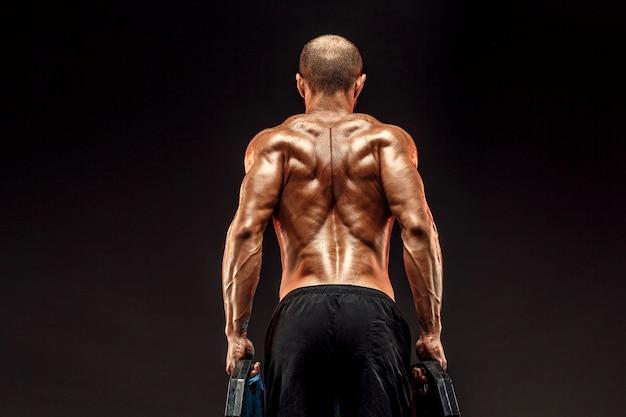 어두운 벽 격리에 그의 등 근육을 보여주는 근육이 벗은 남성 모델.
