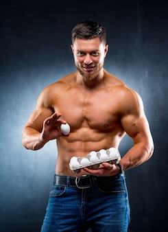 Muscled sportsman is holding one egg and a packaging