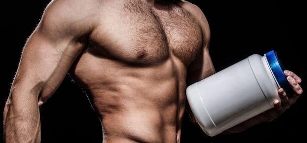 筋肉が強く、筋肉質。ダイエット、フィットネス。筋肉質の体を持つ男はピルを保持します