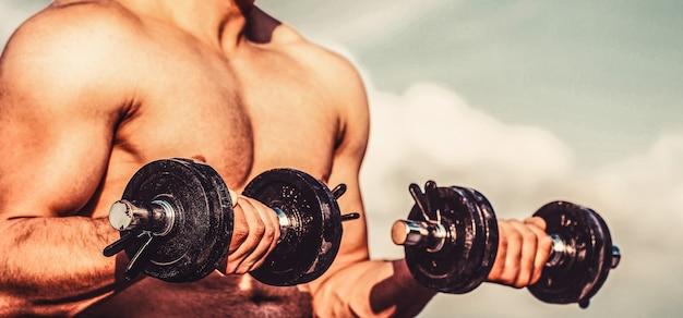 ダンベルの筋肉。ダンベルでトレーニングする男性。ダンベル。筋肉のボディービルダーの人、ダンベルでエクササイズ。