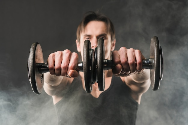 Muscly man holding up weights