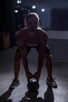 ケツベルを持ち上げる筋肉質の男