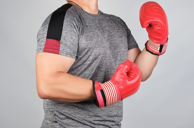 Muscular adult athlete in gray uniform and red leather boxing gloves standing in a rack