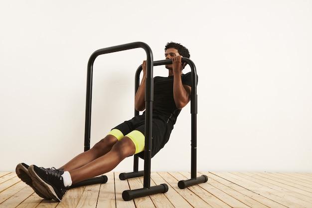 Muscoloso atleta afroamericano in abbigliamento da allenamento nero facendo righe a corpo libero su barre mobili contro il muro bianco e il pavimento in legno chiaro.