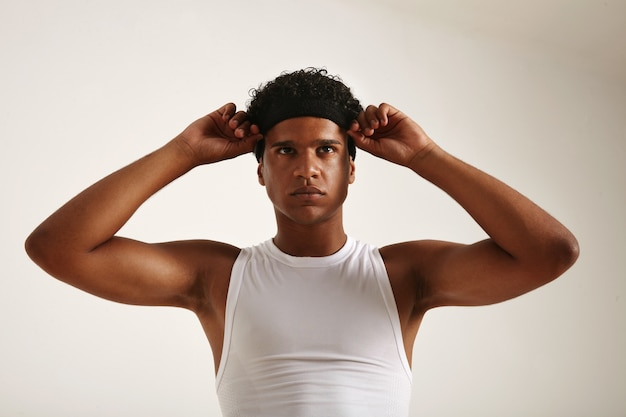 Muscular african american athlete in white basketball shirt adjusting his black headband and looking slightly