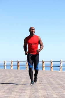 Muscular african man running on seaside promenade