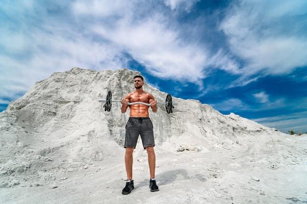 屋外でバーベルを使ってエクササイズをしている筋肉質でひげを生やした男。ボディービルとアウトドアスポーツのコンセプト。採石場での写真撮影。