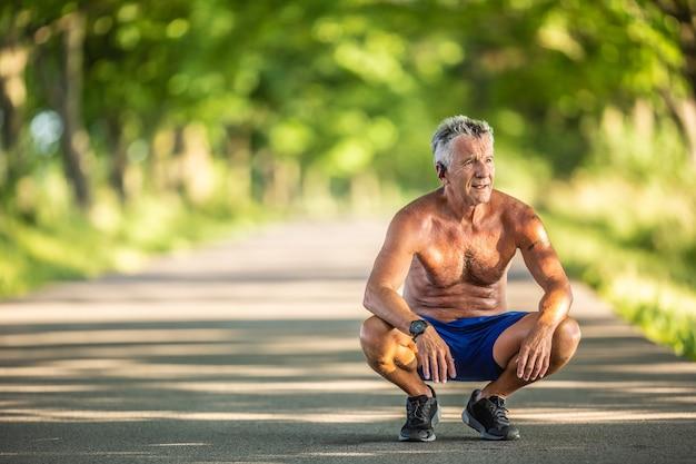自然の中で屋外でスポーツをした後、休むと筋肉質で体にフィットする年配の男性がしゃがみます。