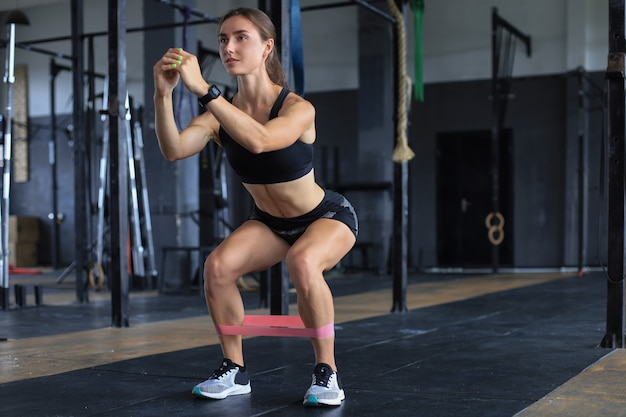 운동을 하는 근육질의 강한 소녀는 체육관에서 피트니스 고무를 사용합니다.