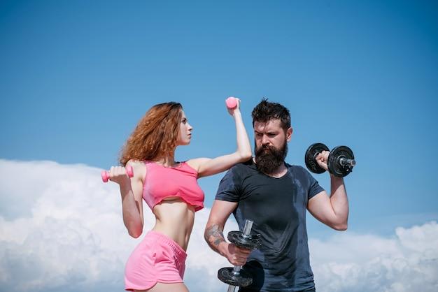 Мускулистый и сильный. сексуальная женщина и хипстер, имеющий мускулистое телосложение и физическую форму. мускулистая пара делает тренировку мышц с гантелями. подходящая девушка и сильный бородатый мужчина, развивающий мышечную силу.