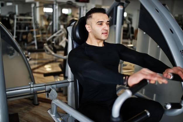 現代のジムでフィットネスマシンのトレーニングとトレーニングを行う筋肉のアラブ人。