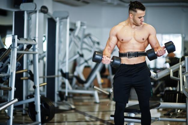 ダンベルモダンジムでトレーニングする筋肉のアラブ人。トレーニングをしている裸の胴体を持つフィットネスアラビア人男性。