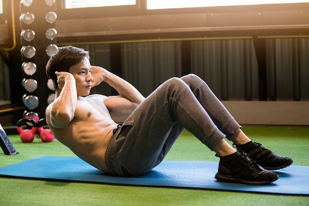 Muscular asian man exercising doing sit up exercise.