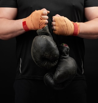 Muscular athlete in a black uniform holds very old black boxing gloves in his hand, his hands are bandaged with an orange elastic sports bandage