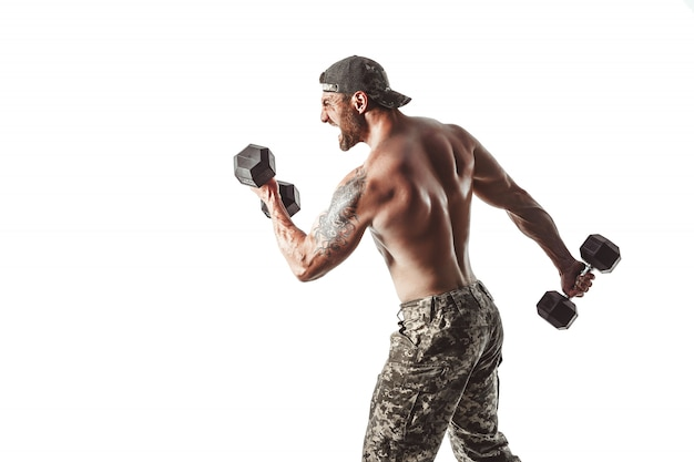 Muscular athlete bodybuilder man in camouflage pants with a naked torso punching with dumbbells like boxer on a white wall