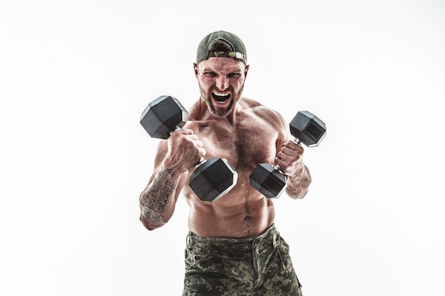 Muscular athlete bodybuilder man in camouflage pants with a naked torso punching with dumbbells like boxer on a white