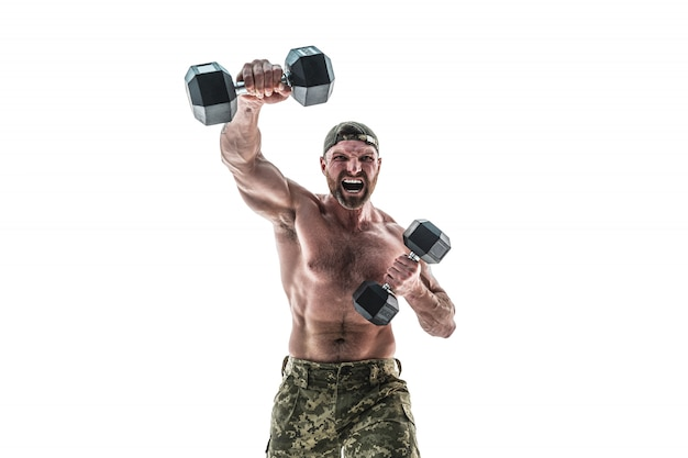 Muscular athlete bodybuilder man in camouflage pants with a naked torso punching with dumbbells like boxer