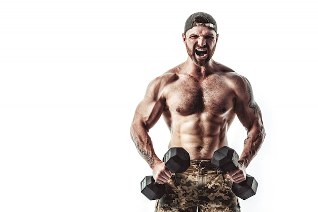 Muscular athlete bodybuilder man in camouflage pants with a naked torso workout with dumbbell on a white wall.