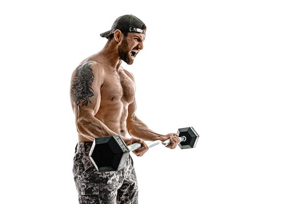 Мускулистый человек культуриста спортсмена в камуфляжных штанах с тренировкой обнаженного торса с гантелями на белой стене. изолировать