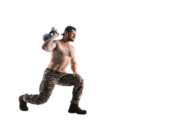흰 벽에 kettlebell와 벌 거 벗은 몸통 운동 위장 바지에 근육 운동 선수 보디 남자. 분리