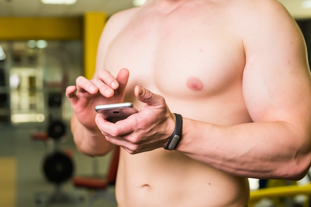 Muscular athlete checking training program on smartphone application after perfect crossfit in gym