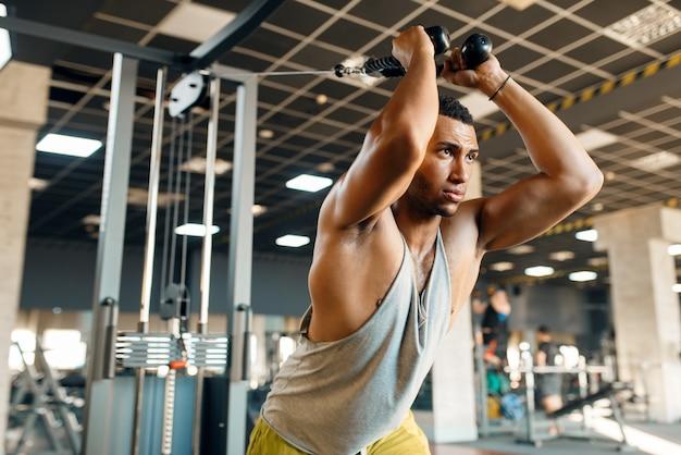 Мускулистый спортсмен в спортивной одежде на тренажере в движении на тренировке в тренажерном зале