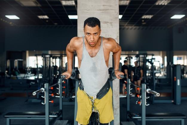 Мускулистый спортсмен в спортивной одежде делает отжимания на брусьях на тренировке в тренажерном зале.