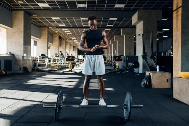 スポーツウェアの筋肉の運動選手は、ジムでトレーニングのバーベルで運動の準備をします。