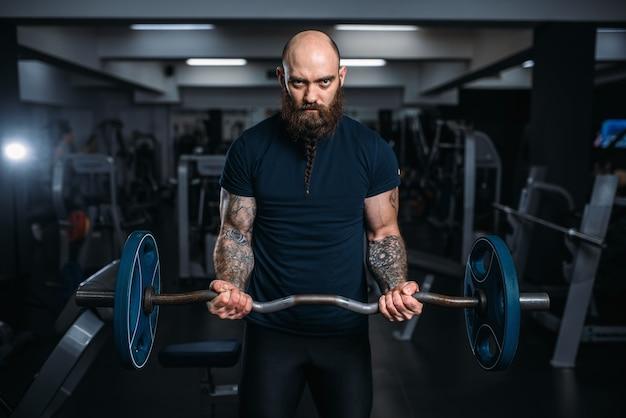 Мускулистый спортсмен в спортивной одежде набирает вес
