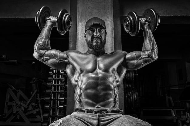 Мускулистый спортсмен поднимает гантели. прокачка плеча. концепция фитнеса и бодибилдинга.
