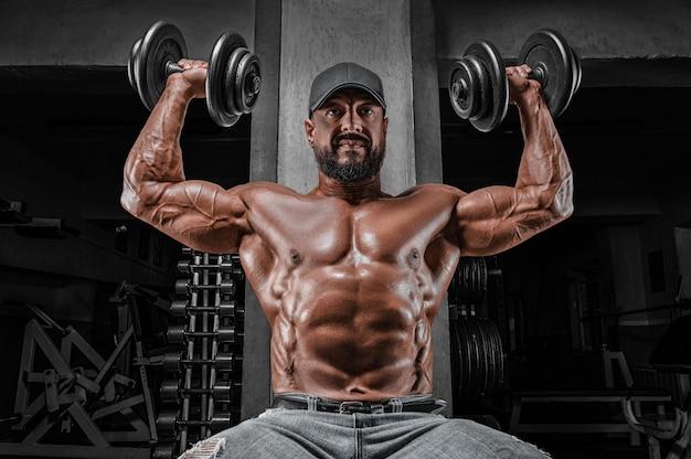 筋肉の運動選手はダンベルを持ち上げます。ショルダーポンピング。フィットネスとボディービルのコンセプト。