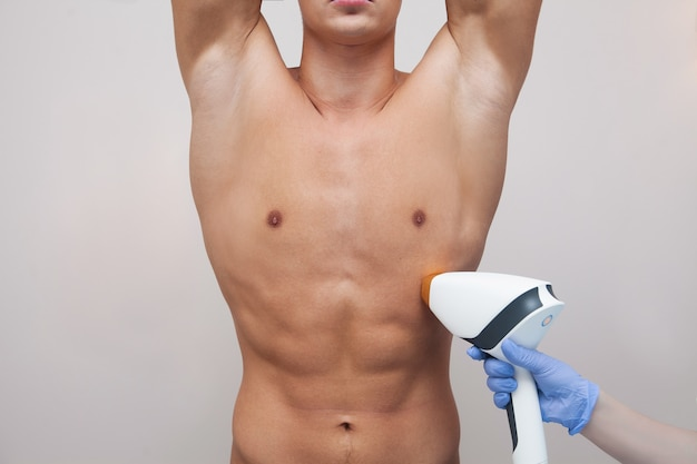 Muscular athlete man holding his arms up and showing underarms, armpit smooth clear skin. epilation and depilation of hair in beauty salon. male laser hair removal concept