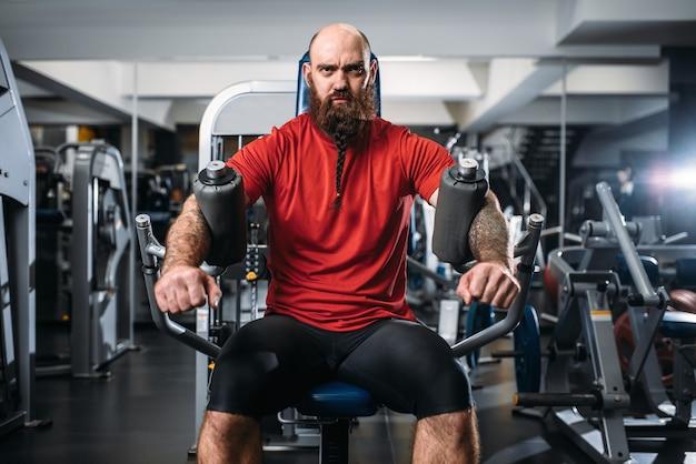Мускулистый спортсмен на тренажере в тренажерном зале