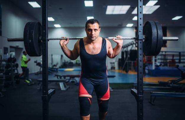 筋肉アスリートがバーベルでスタンドでポーズ