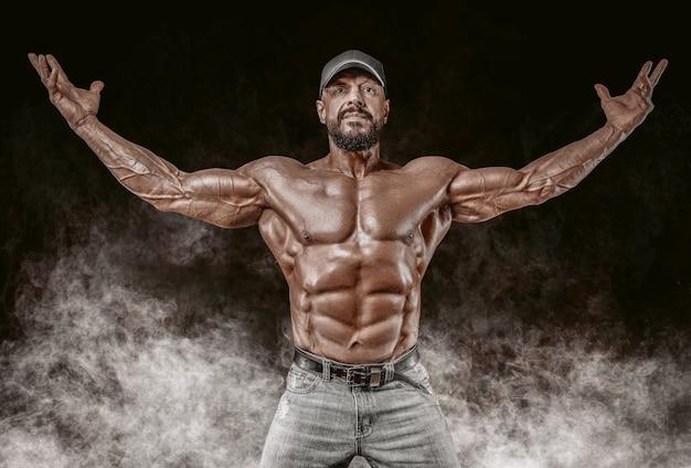 Мускулистый спортсмен позирует. фитнес и классическая концепция бодибилдинга.