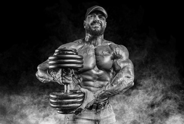 Muscular athlete posing with dumbbells. fitness and classic bodybuilding concept.